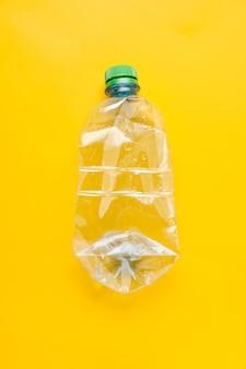 Bottiglia di plastica usata di acqua con tappi su sfondo giallo