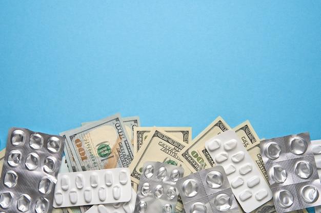 Vesciche e soldi usati della compressa su fondo blu. concerto di medicina costoso
