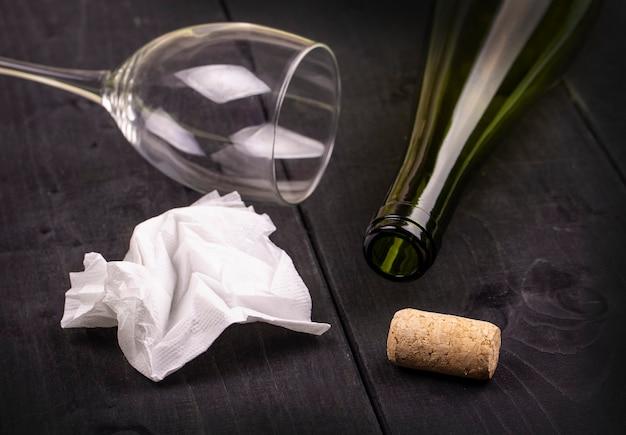 Usato tovagliolo di carta sgualcito bianco e una bottiglia di vino vuota con sughero sul vecchio tavolo di legno