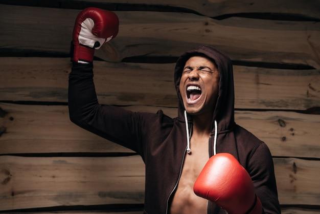Usato per vincere. felice giovane africano in camicia con cappuccio e guantoni da boxe alzando le braccia
