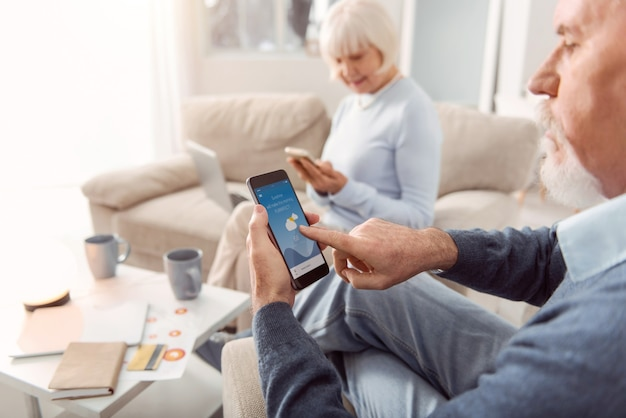 App utile. l'attenzione si concentra su un uomo anziano barbuto seduto sulla poltrona del soggiorno e che controlla le previsioni del tempo nell'applicazione sul suo telefono
