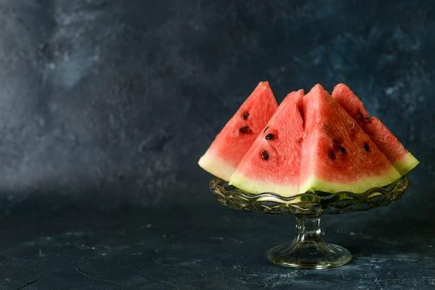 Bacca utile ghiaccioli gustosi dolci una fetta di anguria in estate su uno sfondo rustico blu scuro. copia spazio per il designer