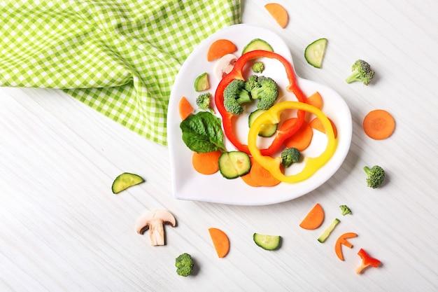 Utile tagliare le verdure su un piatto a forma di cuore sulla tavola di legno