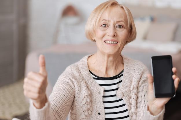 Utile e divertente. donna matura emozionante emotiva che si siede su un divano e che mostra il suo nuovo smartphone mentre si tiene il pollice in su