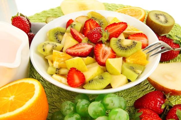 Utile macedonia di frutta fresca e bacche in ciotola sul tovagliolo isolato su bianco