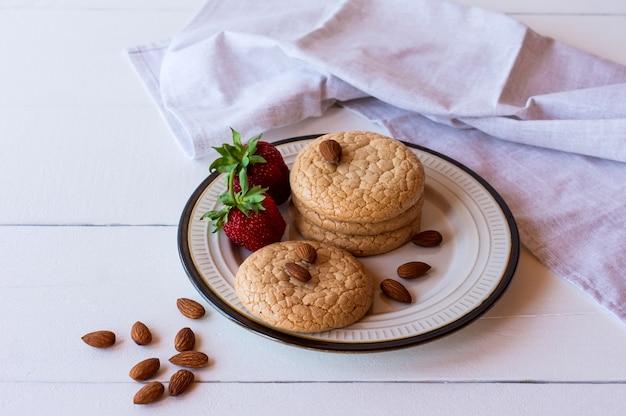 Biscotti quaresimali utili da farina di mandorle con fragola su fondo di legno rustico. messa a fuoco selettiva.