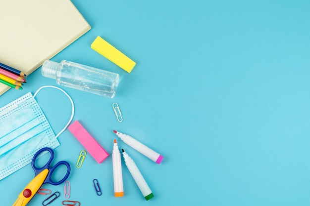 Utile per il ritorno a scuola con maschera e gel disinfettante su sfondo blu. copia spazio.