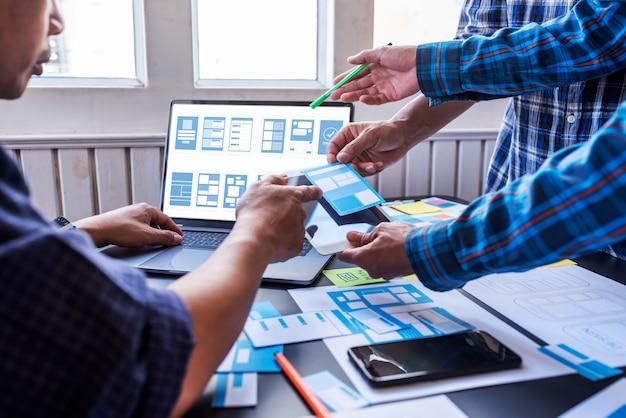 Esperienza utente lavoro di squadra progettisti di ux / ui mobili che lavorano in uno spazio di lavoro collaborativo.