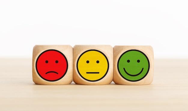 Feedback sul servizio utente, valutazione della recensione del cliente, sondaggio, concetto di sondaggio sulla soddisfazione. blocchi di legno con espressioni facciali