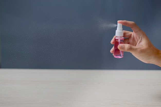 Usando le mani di pulizia con spray alcolico a casa