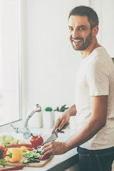 Usando le migliori verdure per la mia insalata. bel giovane che taglia le verdure e sorride mentre sta in cucina