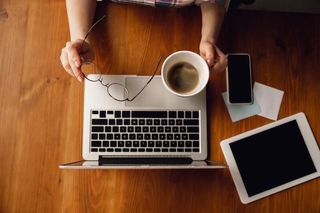 Utilizzo dei dispositivi. primo piano di mani femminili caucasiche, lavorando in ufficio. concetto di affari, finanza, lavoro, acquisti online o vendite. copyspace. formazione, comunicazione freelance.