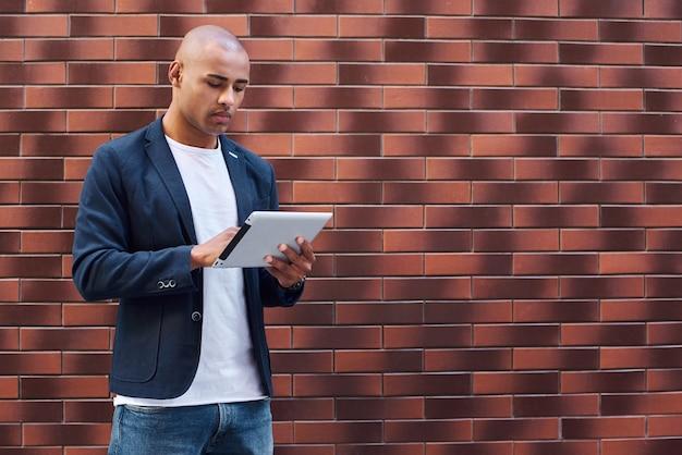Utilizzando gadget giovane ragazzo in piedi sul muro che naviga in internet su tablet digitale concentrato