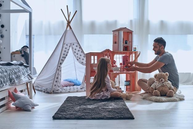Usando l'immaginazione. padre e figlia giocano insieme con una casa delle bambole seduti sul pavimento in camera da letto