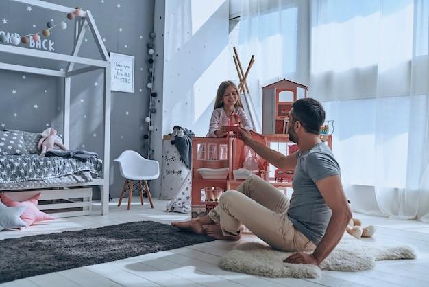Usando l'immaginazione. padre e figlia giocano insieme con una casa delle bambole mentre