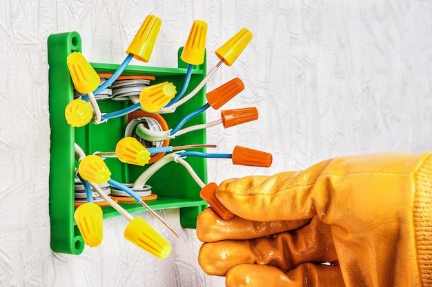 Utilizzo di un morsetto di collegamento isolante o di un dado per cavo di collegamento a torsione per collegare i cavi elettrici in una scatola di distribuzione o di giunzione del cablaggio elettrico residenziale.