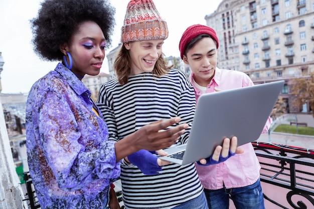 Utilizzando laptop. tre liberi professionisti intelligenti ed eleganti che utilizzano il loro laptop prima di iniziare il progetto