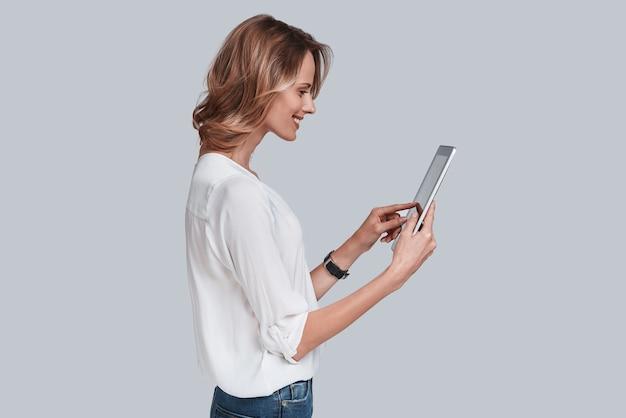 Utilizzando le moderne tecnologie. attraente giovane donna che tiene in mano un tablet digitale e lo guarda mentre è in piedi su uno sfondo grigio gray