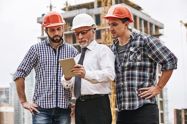 Utilizzando le moderne tecnologie, l'ingegnere senior sta esaminando il piano di progetto su tablet digitale con due