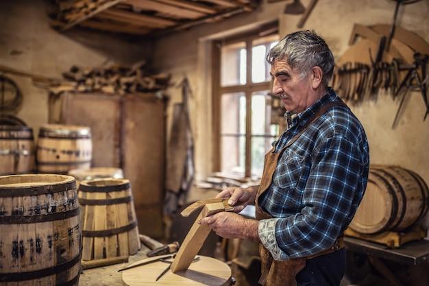 Usando il metodo vecchio stile per costruire botti di legno fatte a mano per liquori.