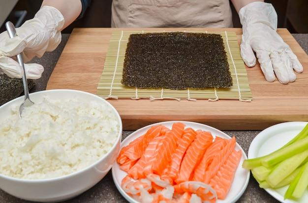 Usando il riso per il sushi, il processo di preparazione del sushi con salmone e avocado