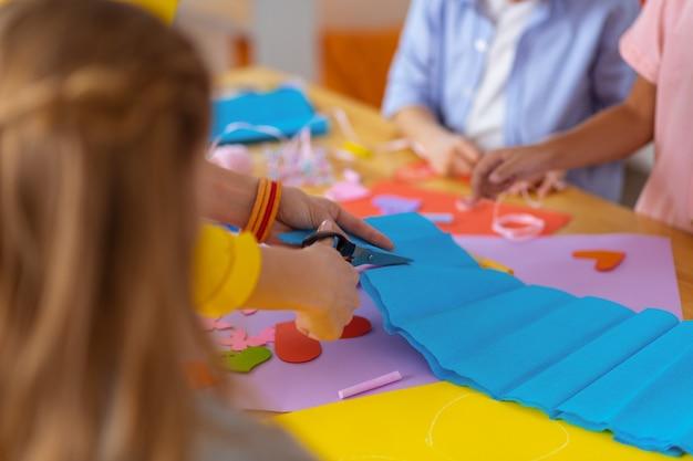 Usando le forbici. primo piano dell'insegnante che indossa braccialetti colorati usando le forbici per tagliare la carta blu