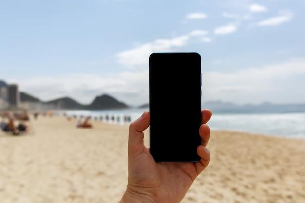 Utilizzando uno smartphone sulla spiaggia. schermo nero vuoto per i tuoi contenuti.