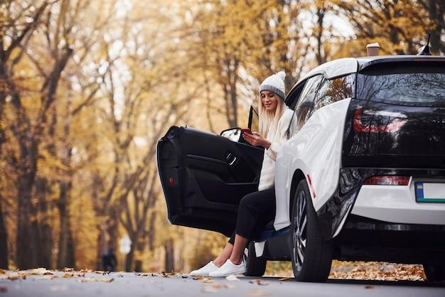 Utilizzo dello smartphone. la ragazza ha un viaggio autunnale in auto. automobile nuova di zecca moderna nella foresta.