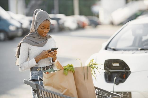 Utilizzo dello smartphone durante l'attesa. donna di etnia africana sulla stazione di ricarica delle auto elettriche durante il giorno. veicolo nuovo di zecca.