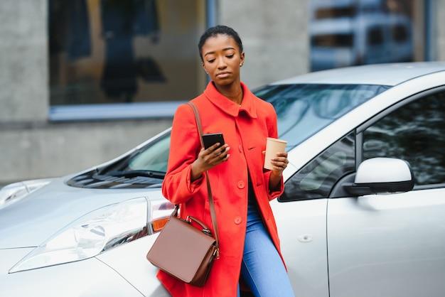 Utilizzo dello smartphone durante l'attesa. donna sulla stazione di ricarica per auto elettriche durante il giorno. veicolo nuovo di zecca.
