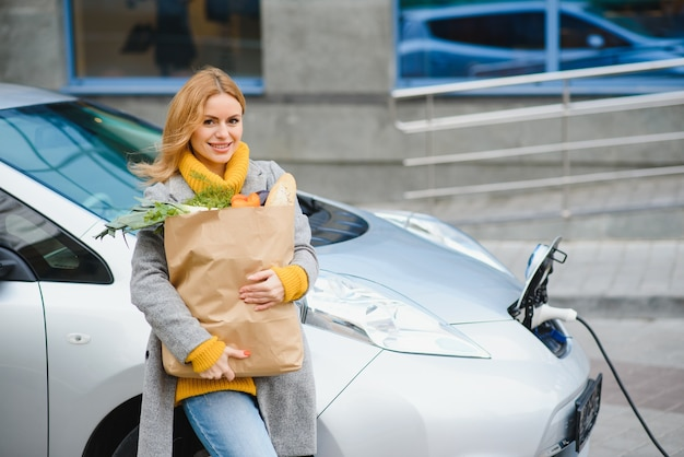 Utilizzo dello smartphone durante l'attesa. donna sulla stazione di ricarica per auto elettriche durante il giorno
