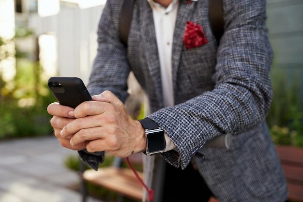 Utilizzando le tecnologie in prossimità delle mani di un elegante uomo d'affari di mezza età che utilizza il suo smartphone mentre
