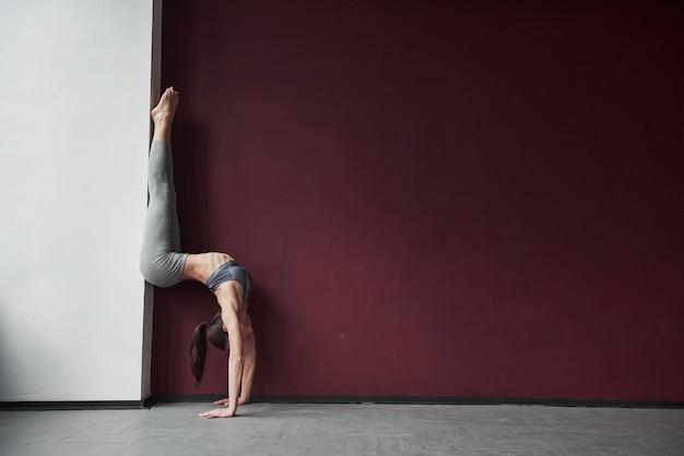 Usando il muro per rendere questo tratto incredibile. la ragazza con un buon tipo di corpo fitness ha esercizi nella stanza spaziosa