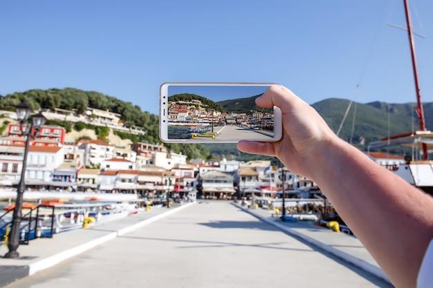 Usa il tuo smartphone come fotocamera mobile mentre sei in viaggio. porto della città di mare sullo schermo.