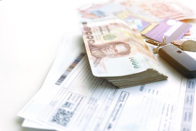 Bollette, banconote thailandesi e carte di credito per il pagamento