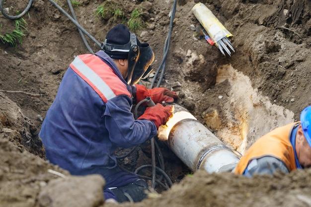 Operaio di servizio che ripara il concetto di riparazione del tubo di fognatura principale dell'acqua rotta