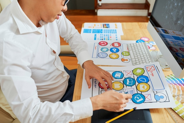 Ux designer che riorganizza le icone sul layout dell'applicazione mobile quando parla con il project manager