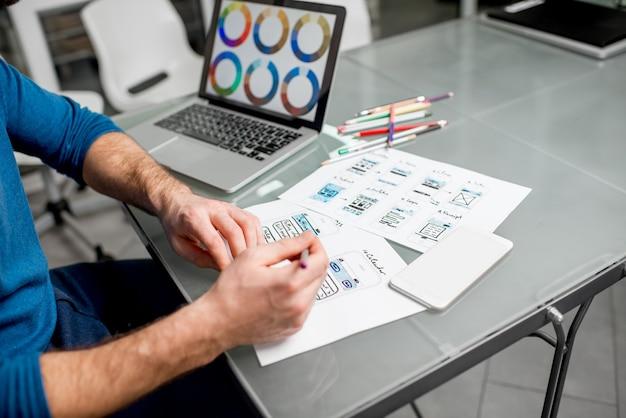 Designer ux che lavora sull'esperienza dell'applicazione mobile disegnando disegni in ufficio. immagine focalizzata senza i disegni ritagliati senza volto