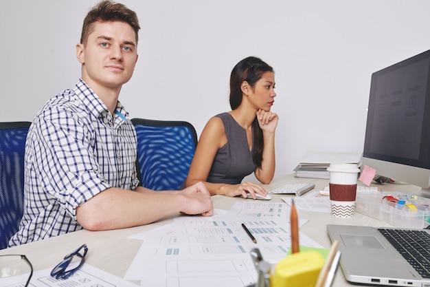Designer di ux e ui seduti uno accanto all'altro quando lavorano sull'interfaccia per una nuova applicazione mobile