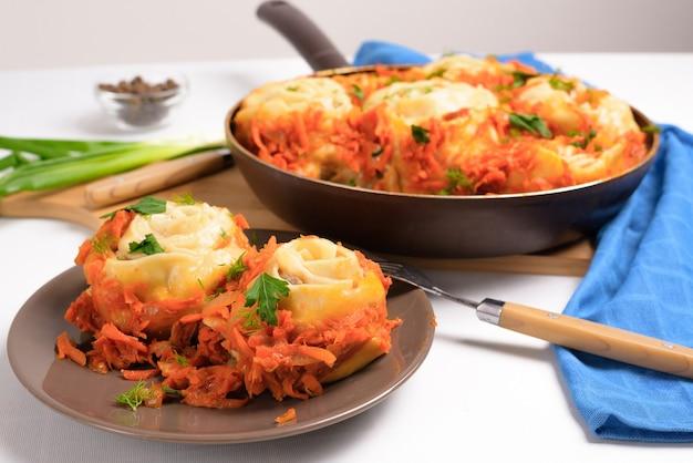 Manti uzbeko a casa in una padella con verdure stufate, ingredienti - carne, verdure, pasta. vista dall'alto su sfondo chiaro.