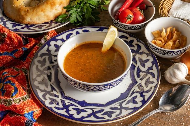 Zuppa uzbeka a base di lenticchie, cipolle, menta e concentrato di pomodoro. servito con limone e pane pita fritto