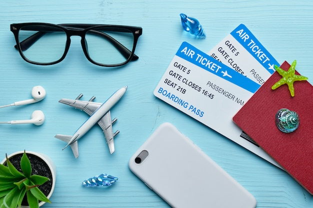 Concetto di vacanza - aeroplano, smartphone e passaporto con i biglietti aerei su di legno blu
