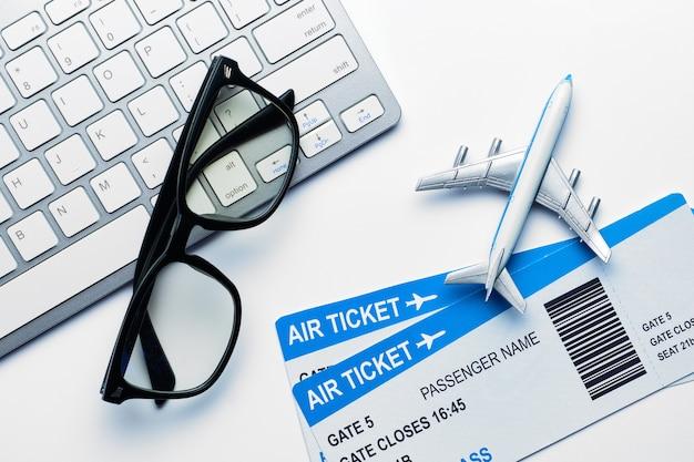 Concetto di vacanza - occhiali, biglietti aerei, aereo con una tastiera con una vista dall'alto