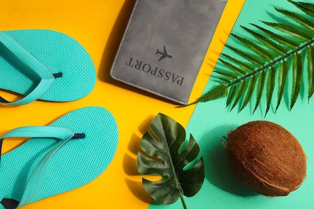 Concetto di vacanza composizione estiva con monstera di cocco e foglie di palma passaporto e infradito su texture giallo brillante e turchese vista dall'alto piatta