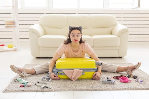 Concetto di vacanza, viaggio e vacanze - donna che raccoglie vestiti sul pavimento.