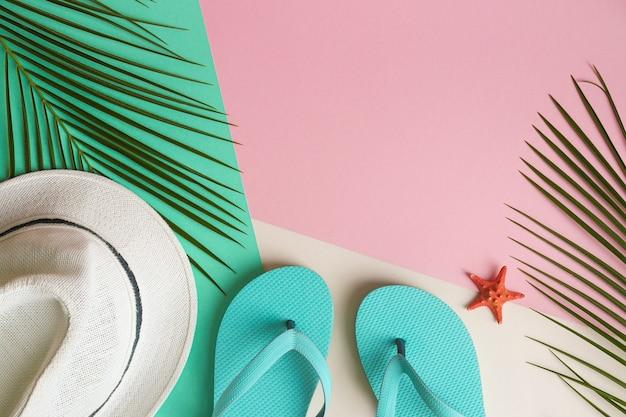 Concetto di vacanza ed estate foglie di palma cappello estivo infradito e conchiglia con spazio copia