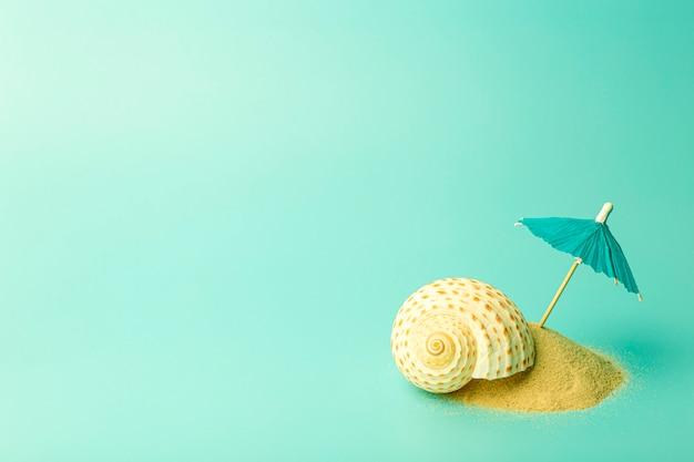 Fondo di concetto di vacanza, estate, relax e mare. composizione creativa minima con sabbia e ombrello su uno sfondo colorato pulito.