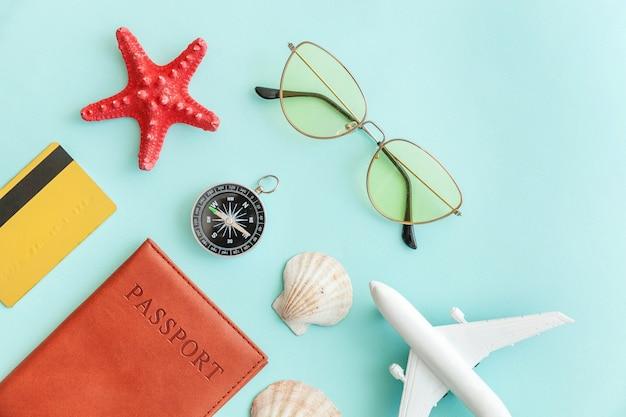 Concetto di viaggio avventura viaggio vacanza. minimo piatto semplice laici con passaporto aereo occhiali da sole bussola oro guscio di carta di credito su sfondo blu pastello colorato alla moda.