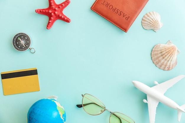 Concetto di viaggio avventura viaggio vacanza. minimo piatto semplice laici con passaporto aereo occhiali da sole globo oro carta di credito e guscio su sfondo blu pastello colorato alla moda