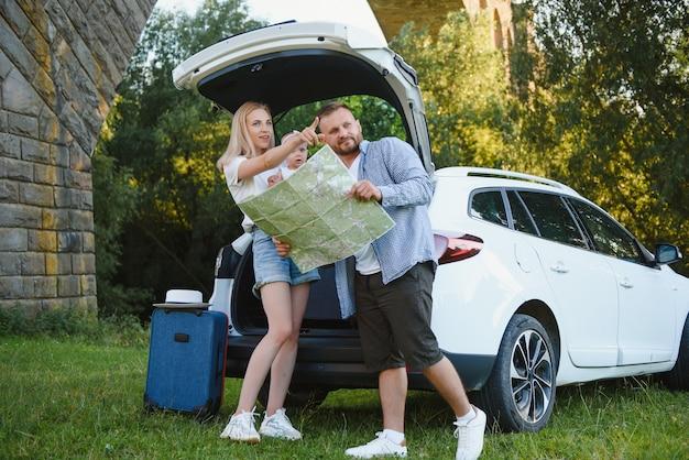 Vacanze, viaggi - famiglia pronta per il viaggio per le vacanze estive. valigie e percorso auto. persone con mappa in mano che pianificano un viaggio su strada. concetto di viaggio. viaggiatore.